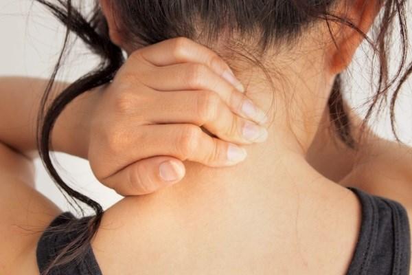 Женщина трет шею